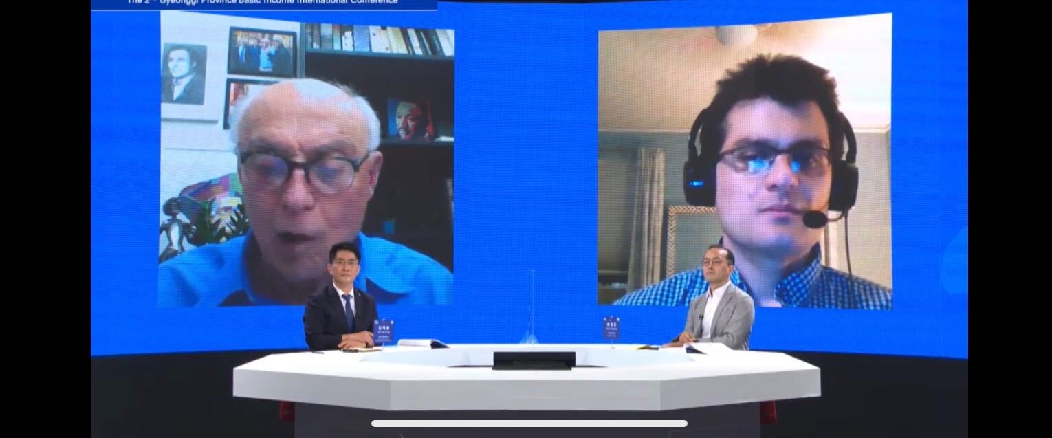 Stephen Nuñez and Eduardo Suplicy appear on a large screen behind the moderators.
